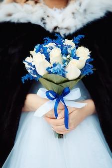新鮮なカラスリリーの花束を持って花嫁。創造的な冬のウェディングブーケ