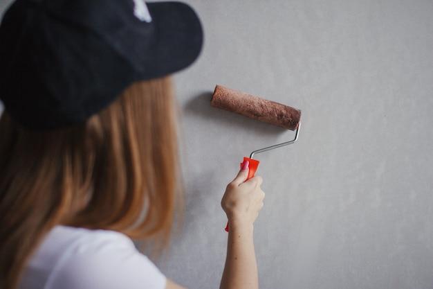 Малярный валик в руке молодой женщины кавказа перед новой стеной в комнате.