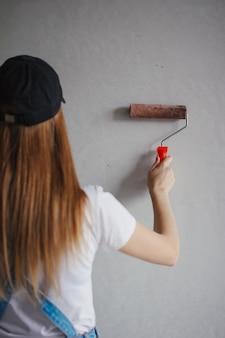 部屋の新しい壁の前で若い白人女性の手でペイントローラー。