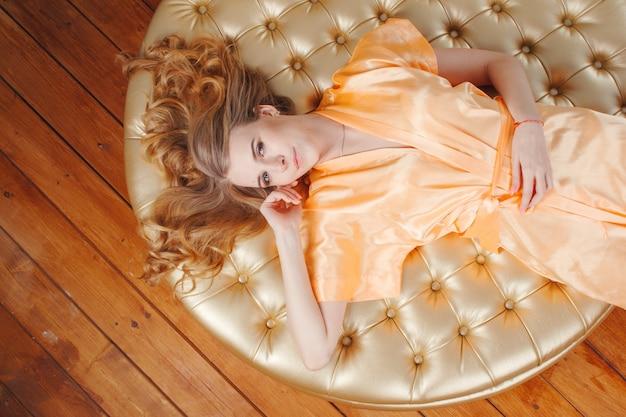 丸いプーフの上に敷設桃シルクローブで美しい金髪の女性。上からの眺め