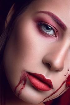 顔にアップリケの赤いバラの花を持つ美しい少女