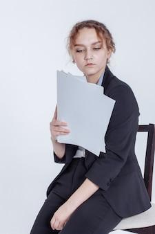 古典的なスーツの若いサラリーマンの女の子は、白の紙のきれいなシートを保持しています。