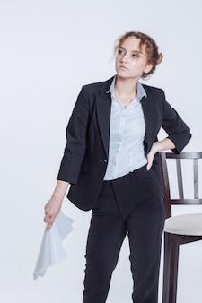 古典的なスーツの若いサラリーマンの女の子は、白で隔離紙のきれいなシートを保持します。