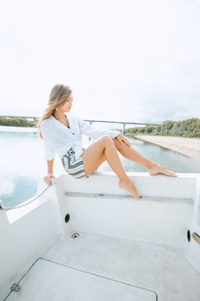 海のヨットでリラックスできる豪華な服で長い脚を持つ女性