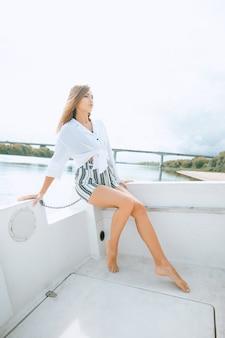 豪華なヨットでポーズをとって、彼女の長い脚を示すファッションモデル