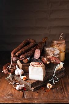 Копченая свиная колбаса. ребрышки на спине, белый хлеб, кукурузный хлеб, печеные бобы, картофельный салат и т. д. традиционные различные копчености и мясо барбекю. ассорти колбасных изделий из мяса, украшенных чесноком и перцем