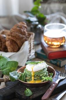 Завтрак шпинатные блины с яйцом-пашот на деревянном столе