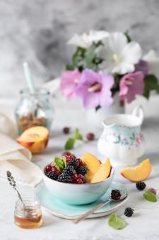グラノーラまたはミューズリーとベリーとフルーツ。朝は健康的な朝食に、ライトテーブルには夏の花束が。