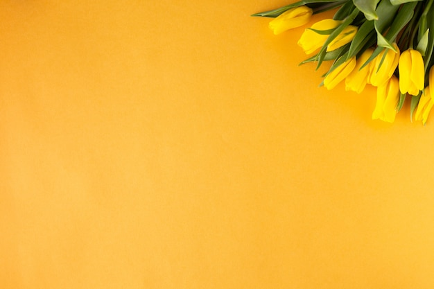 美しいフラワーアレンジメント。黄色の花チューリップ、黄色の背景上のテキストの空のフレーム。結婚式。誕生日バレンタインデー。母の日。フラット横たわっていた、トップビュー、コピースペース