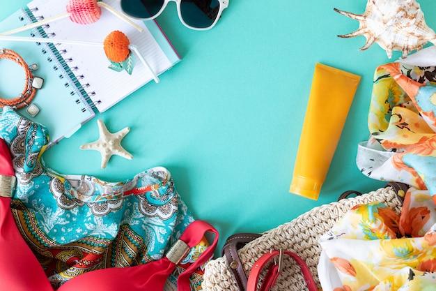 カラフルな夏の女性のファッションのアパートの服。ストローバッグ、サングラス、ヤシの枝、レモンとライムと青色の背景、上面図、幅広い構成の水。夏のファッション、休暇の概念