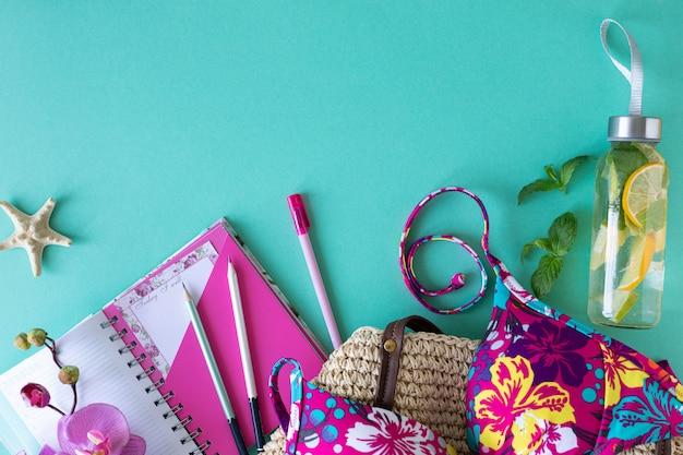 カラフルな夏の女性のファッションのアパートの服。ストローバッグ、サングラス、ヤシの枝、青色の背景、上面図、幅広い構成。夏のファッション、休暇の概念