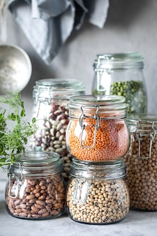ガラスの瓶、コンクリートの白いテーブルに異なる豆類のセットです。菜食主義者のためのタンパク質の源。健康的な食事と食品保管のコンセプト。