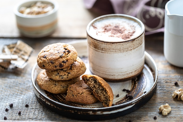 Домашнее печенье с орехами и кофе в керамической чашке
