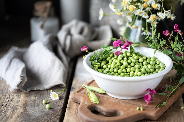 Молодые зеленые горохи в белом шаре на деревянной предпосылке. цветы гороха и цветы ромашки на столе.