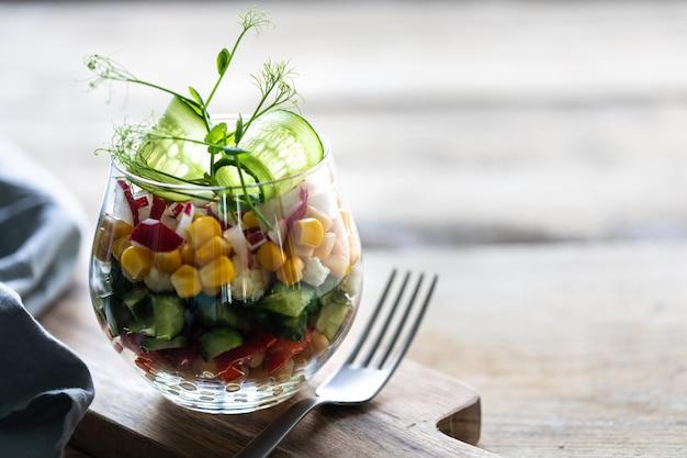 Салат весеннего овоща в стеклянной чашке на деревянной предпосылке. правильное питание. копировать пространство вертикальная. выборочный фокус.
