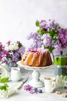 明るい表面の果実と花束とライラックの自家製カップケーキ。垂直