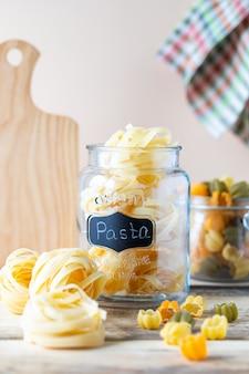 黄色の木製のテーブルの上のガラスの瓶にイタリアンパスタの種類