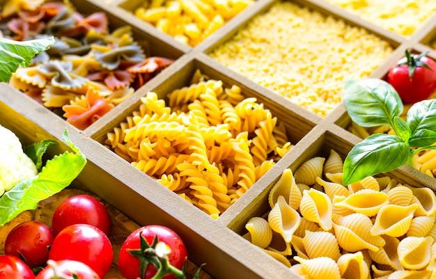 木製の箱でイタリアの生パスタ、全粒小麦のパスタ、パスタ、スパゲッティ、麺、タリアテッレの種類。上面図。