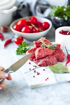 Сырцовый свежий мраморизованный стейк мяса и и вилка мяса на белой мраморной предпосылке. нож в мужской руке