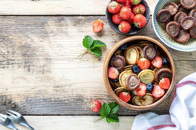 蜂蜜と木製の背景にイチゴを木製のボウルに小さなパンケーキシリアルとチョコレートのミニパンケーキ。上面図。コピースペース。トレンディな食べ物