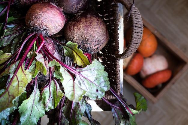 木製のテーブルの枝編み細工品バスケットの葉を持つ新鮮な有機赤ビート。天然有機野菜。秋の収穫。素朴な