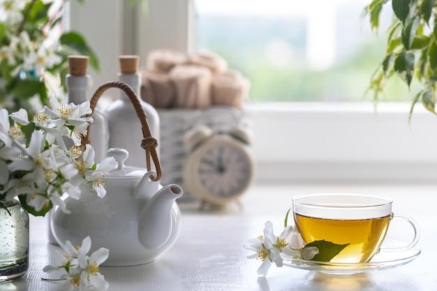 白い背景にジャスミンの花で作られたお茶を自宅でスパリゾート。コピースペース。スパとウェルネスのコンセプトです。
