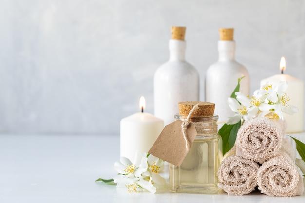 ジャスミンのエッセンシャルオイル、キャンドル、タオル、白い背景の上の花。スパとウェルネスのコンセプトです。コピースペース。