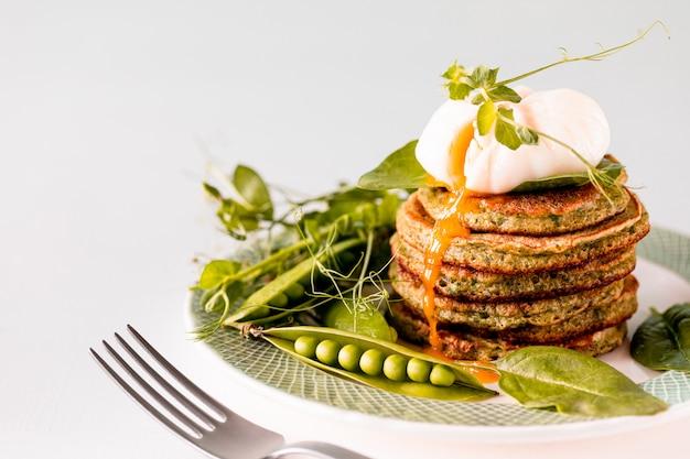 ほうれん草とポーチドエッグのグリーンパンケーキ。おいしい健康的なヨーロッパの朝食。コピースペース。