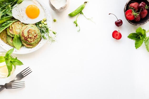 おいしい健康的な朝食。ほうれん草、卵、若いグリーンピースのグリーンパンケーキ。上面図。コピースペース
