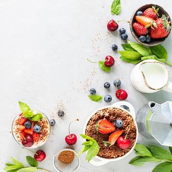 ティラミスイタリアのデザートと食材。コーヒー、ココア、イチゴ、白い背景の上のミント。コピースペースの上面図