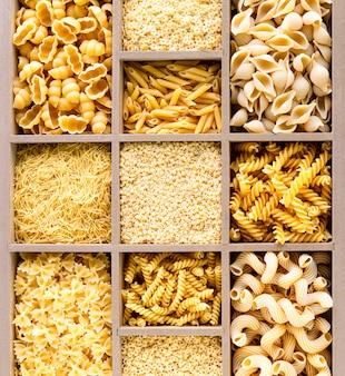 Различные виды итальянских сырых макарон в деревянной коробке, макароны из цельной пшеницы, макароны, спагетти, лапша, тальятелле. вид сверху.