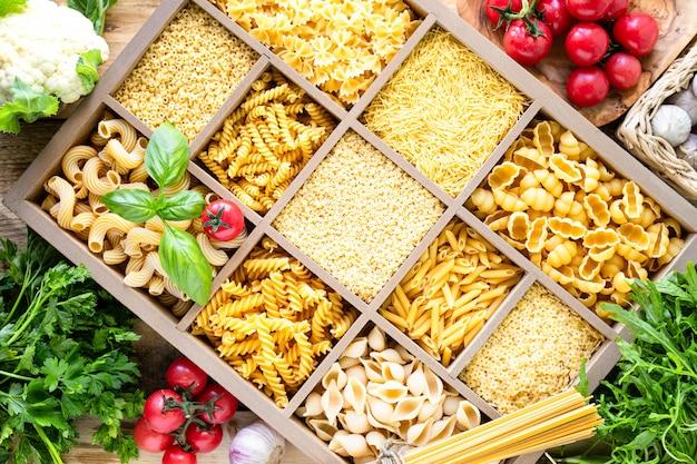 Разные виды итальянских сырых макаронных изделий в деревянной коробке. вид сверху.