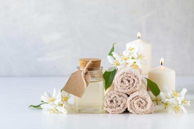 ジャスミンのエッセンシャルオイル、キャンドル、タオル、花。スパのコンセプトです。