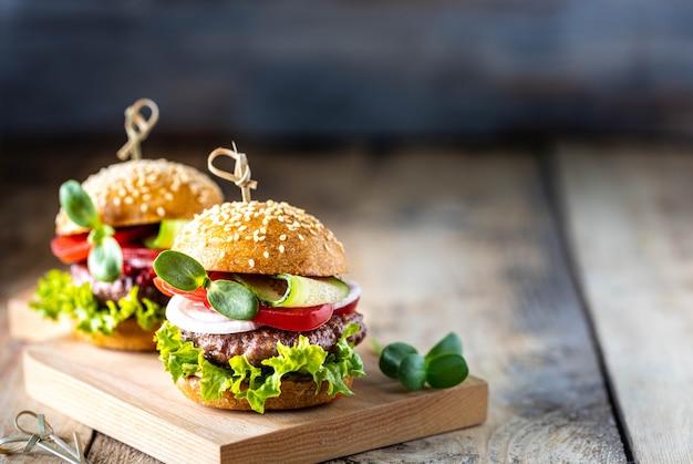 カツレツ、新鮮なレタス、トマト、木製のテーブルに玉ねぎと自家製ハンバーガー。コピースペース