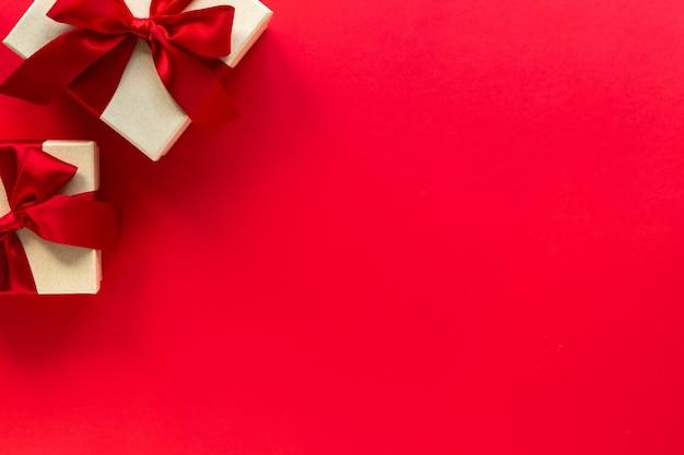 Две подарочные коробки с красным бантом на красном, вид сверху с копией пространства
