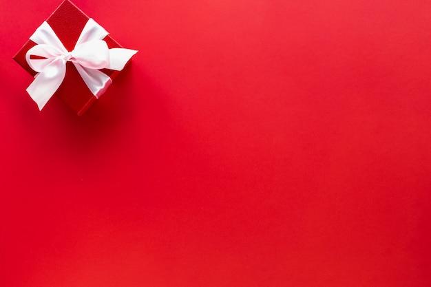 Подарочная коробка с белым бантом на красном, вид сверху с копией пространства