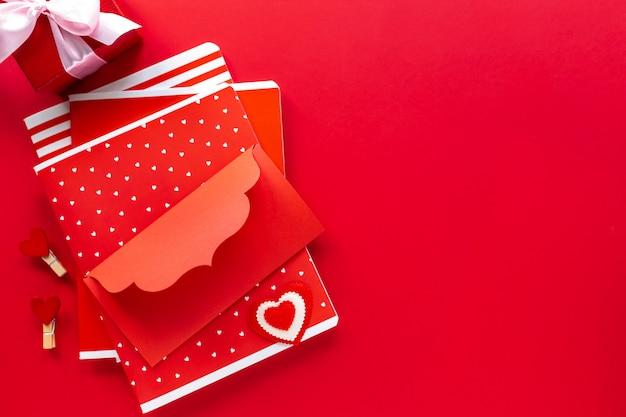 赤いノート、封筒、ギフトボックスコピースペース付きの赤いテーブルに弓を持つボックス。上面図