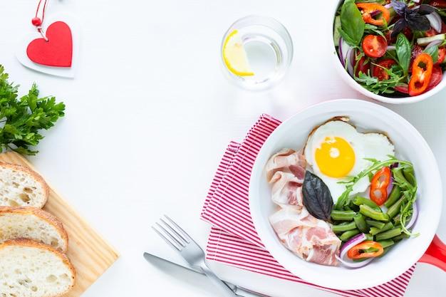 休日の最愛の人のための朝食:ハート型の卵、ベーコン、白いテーブルに緑色の豆。セレクティブフォーカス。上面図。コピースペース