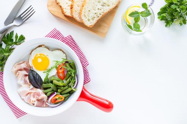 ヨーロッパの朝食:ハート型の卵、ベーコン、インゲン、白いテーブルの上。セレクティブフォーカス。上面図。コピースペース