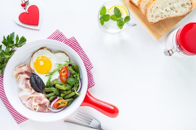 休日の最愛の人のための朝食:ハート型の卵、ベーコン、白いテーブルの上の緑の豆。セレクティブフォーカス。上からの眺め。スペースをコピーします。