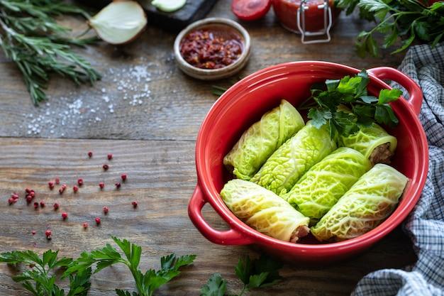 Савойские голубцы, фаршированные мясом, рисом и овощами на деревенском столе.