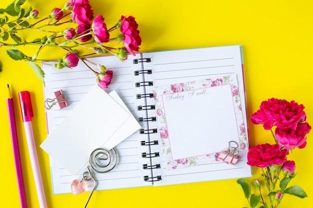 Планер с заметками и списком дел на желтом фоне с розовыми канцелярскими принадлежностями и цветами. бизнес-концепция. вид сверху