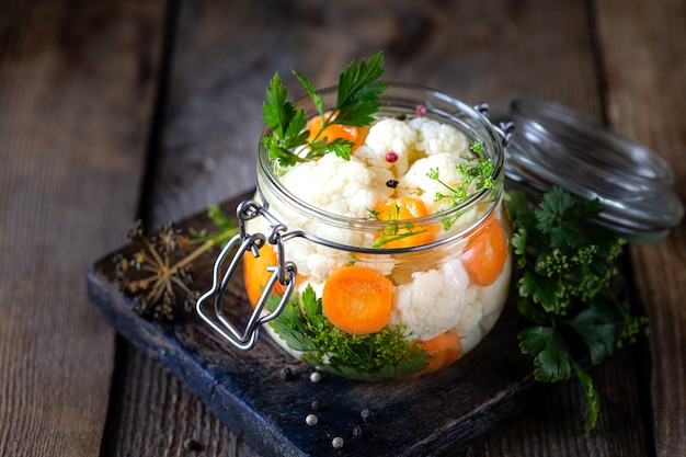 Маринованная цветная капуста с морковью в стеклянной банке на темный деревянный стол.