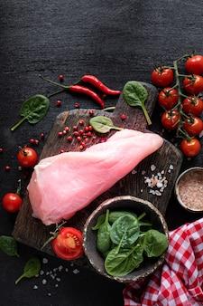 生の七面鳥の切り身を焼く準備ができています。チェリートマト、唐辛子、ほうれん草の葉、緑の木製のまな板の上の鶏の切り身。