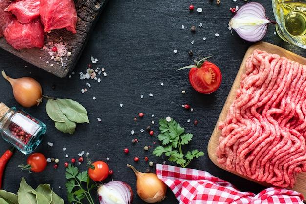 Филе телятины и фарш на деревянной разделочной доске с помидорами черри, острым перцем и зеленью.