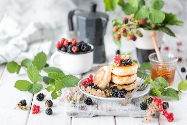 ベリー、ブラックベリー、プレート上の蜂蜜、白い木製の背景にブラックベリー目覚まし時計の枝と自家製パンケーキ