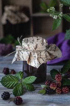 Стеклянная банка с соусом из ежевики крупным планом. ветка с ягодами и листьями в деревянной резной коробке на фоне темных деревянных.
