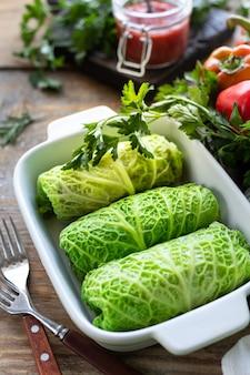 素朴なテーブルの上に肉、米、野菜を詰めたサボイキャベツロール