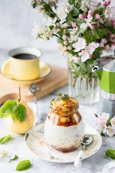 ナチュラルヨーグルトと新鮮でカラメル梨と花の花束と白いテーブルの自家製グラノーラ。