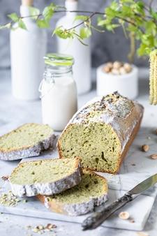 Фисташковый ореховый торт со шпинатом и чашкой кофе на белом мраморном столе. закрыть